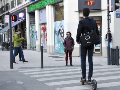 Jeune homme à trottinette qui attend au passage piéton, à Grenoble. © Muriel Beaudoing - placegrenet.fr