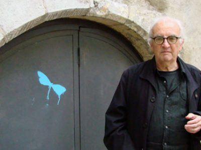 L'écrivain grenoblois Arthur Bernard auteur de Gaby et son maître devant une porte en fer noir avec un pochoir de libellule bleu à Grenoble