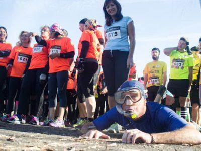 Participants juste avant le départ de la course d'obstacles Mud Gre à Grenoble le 8 novembre 2015 avec un coureur allongé au sol avec tuba et lunettes de plongée. © Yuliya Ruzhechka - placegrenet.fr