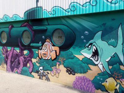 Fresque murale dans le quartier Mistral à Grenoble : une pieuvre retient un sous-marin devant un poisson clown inquiet et un requin agressif toutes dents dehors. © Ludovic Chataing - placegrenet.fr