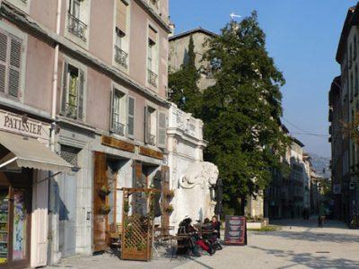 Le début de la rue Saint Laurent à Grenoble avec une terrasse devant l'écomusée et la devanture d'un boulanger patissier © Delphine Chappaz - placegrenet.fr
