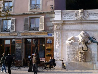 Place de la cymaise à Grenoble au début de la rue Saint Laurent avec vue sur L'Eco' Musée Le Mont Rachais et la fontaine au lion © Delphine Chappaz - placegrenet.fr